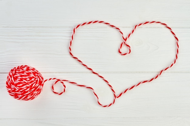 赤い羊毛糸からのハートの形。白い木製の背景に赤いウール糸で作られたハート。木製の背景に編むためのウールのボール。ハッピーバレンタインデー。