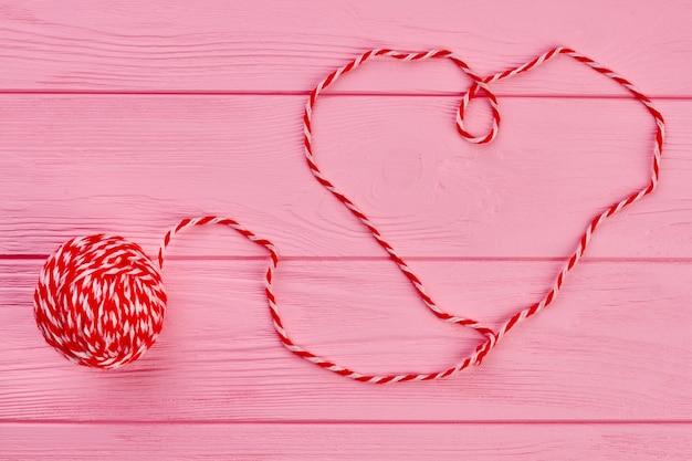 빨간색 모직 스레드에서 심장의 모양입니다. 핑크 나무 배경에 원사의 공입니다. 발렌타인 데이 개념.