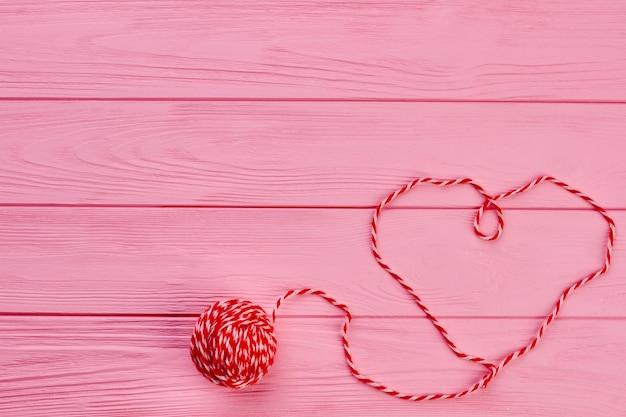 모직 실에서 심장의 모양. 나무 배경 및 복사 공간에 심장 모양을 형성하는 모직 스레드. 원사의 공. 발렌타인 데이 휴일 인사말에 대한 아이디어.