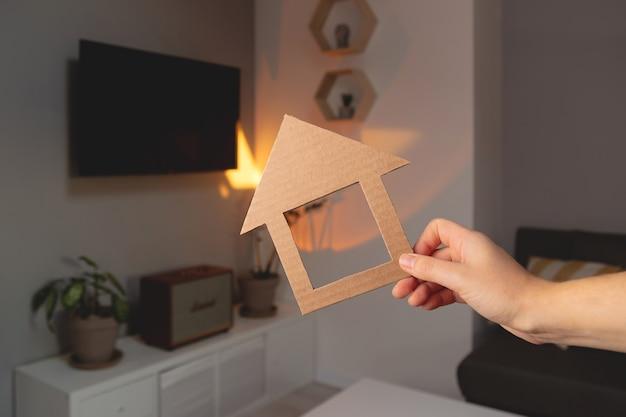 新しいアパートのリアルなエスタのミニマルなインテリアを背景にした女性の手の家の形...