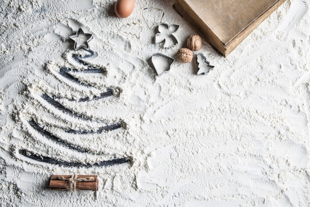 Shaped christmas tree of flour old recipe book eggs walnuts and baking utensil.