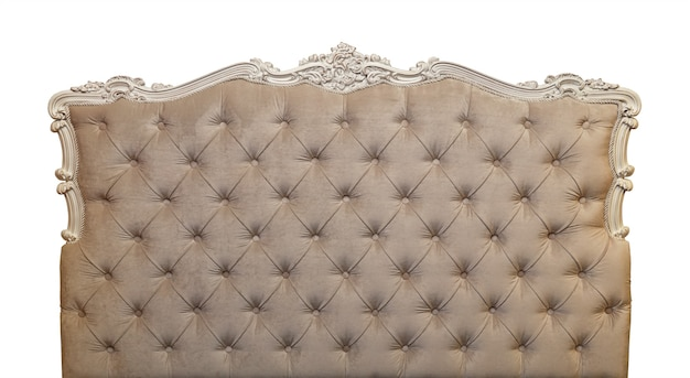 Shaped pastel beige color soft velvet fabric capitone bed headboard of chesterfield style sofa with carved wooden frame, isolated on white background, front view