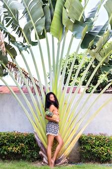 日光浴後にエキゾチックなリゾートでポーズをとって光沢のある肌を持つ格好良いアジアの女の子。ヤシの木の近くに立って興味を持って探しているトレンディなビキニでヒスパニック系ブルネットの女性。