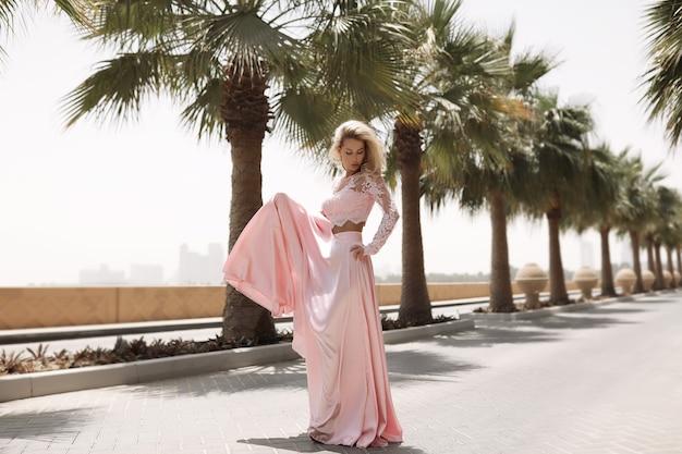 ドバイの海の横にある格好の良いブロンド、ヤシの木、暑くてゴージャスなドレス、夏の日当たりの良いライフスタイルのファッション撮影、風のドレスで手を振る、プールの近くで落ち着いてリラックスする、髪型、メイク