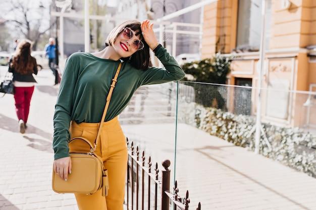通りに立っている明るい化粧をした格好の良いブルネットの女性。春の町でポーズをとって流行の髪型を持つ幸せな女の子の屋外の肖像画。