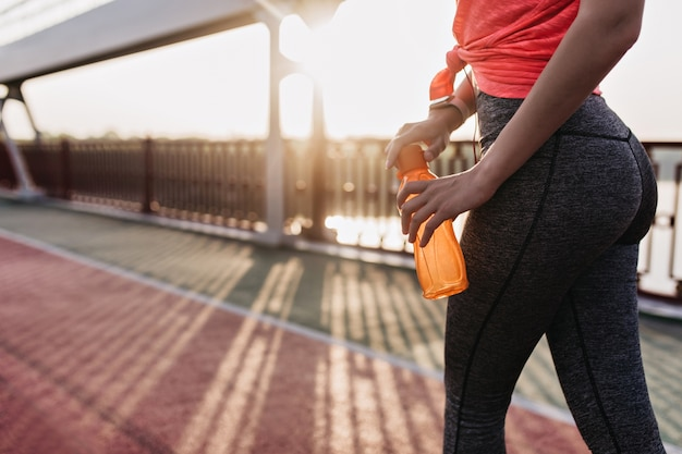 Shapely caucasian lady drinking water after training. outdoor portrait of european girl in sport pants doing exercises.