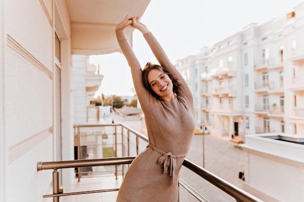 バルコニーで伸びる茶色のドレスを着た格好の良い白人女性。テラスで朝を楽しんでいる夢のようなブルネットの少女。