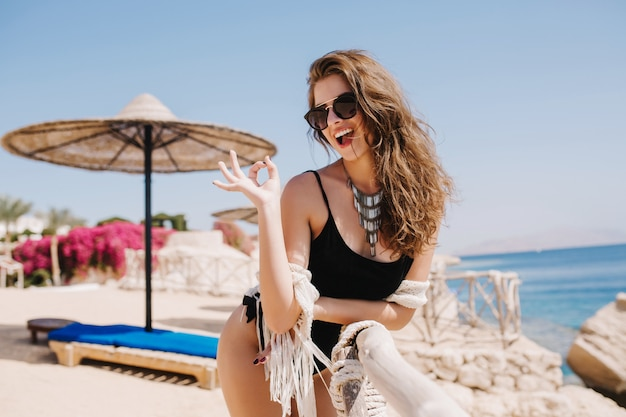 Shapely cheerful girl in black bodysuit laughing and posing with okay sign on the sea beach. attractive young lady in trendy necklace cute smiling and having fun on resort in summer weekend.