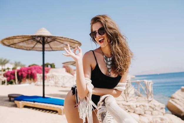 Стройная жизнерадостная девушка в черном боди смеется и позирует с хорошо знаком на морском пляже. привлекательная молодая леди в модном ожерелье мило улыбается и веселится на курорте в летние выходные.