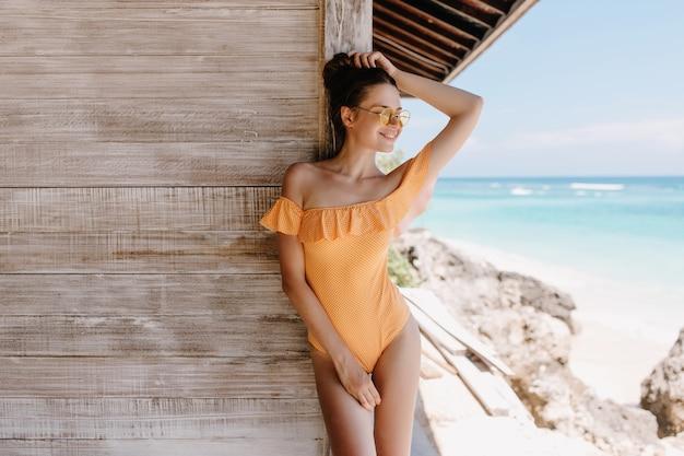 インスピレーションを得た顔でビーチでポーズをとるオレンジ色の服装の形の良い陽気な女の子。ビーチの木造住宅の横に立っているサングラスをかけた壮大な若い女性の屋外写真。