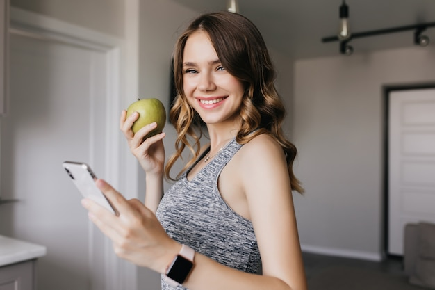 Shapely cute girl posing with green apple at home. indoor photo of blissful curly woman holding smartphone with smile.