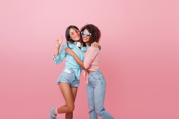 Shapely dark-haired young woman in vintage jeans embracing brunette european girl. indoor portrait of slim asian lady in denim shorts standing with ecstatic face expression.