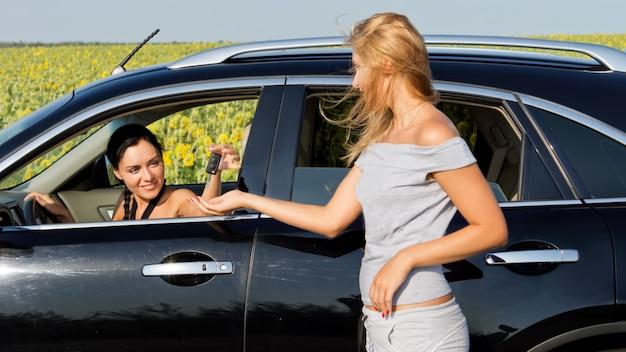 車の中で美しい笑顔の女性ドライバーと話し、開いている窓から彼女に何かを渡す形の良いエレガントなブロンドの女性