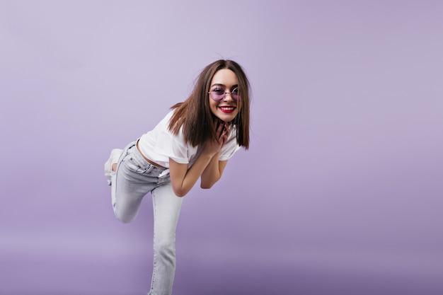 Стройная европейская женщина в белых джинсах стоит на одной ноге и дурачится. крытый портрет танцующей женской модели в солнечных очках.