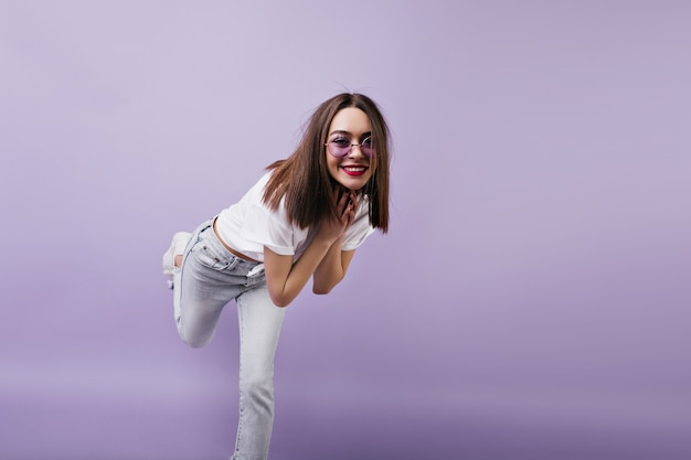 Shapely european woman in white jeans standing on one leg and fooling around. indoor portrait of dancing female model in sunglasses.