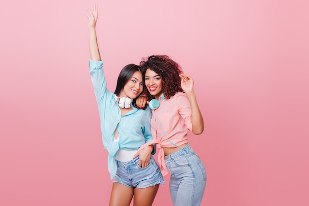 Shapely european woman with bronze skin dancing with hands up near mulatto female friend. charming ladies in jeans and cotton shirts relaxing.