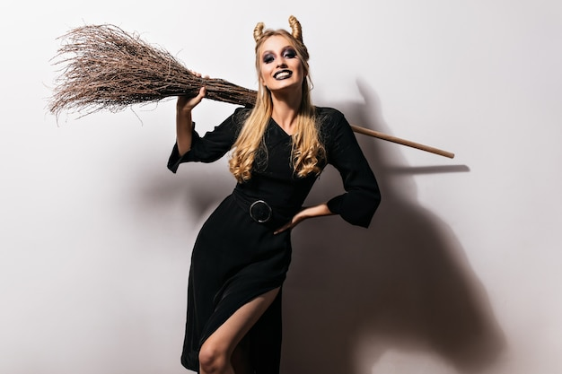 검은 화장과 함께 포즈 매끈한 여성 뱀파이어. 할로윈 파티에서 놀 아 요 빗자루와 매력적인 마녀.