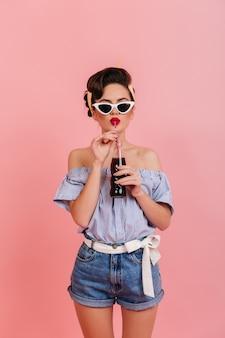 데님 반바지와 스트라이프 블라우스 음료를 마시는 매끈한 소녀. 선글라스에 핀 업 레이디의 스튜디오 샷입니다.