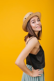 エレガントなタンクトップの笑顔で格好の良い女の子。麦わら帽子の女性ブルネットモデルの屋内写真。