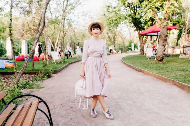 Стройная девушка в модной шляпе стоит со скрещенными ногами возле деревянной скамейки в парке