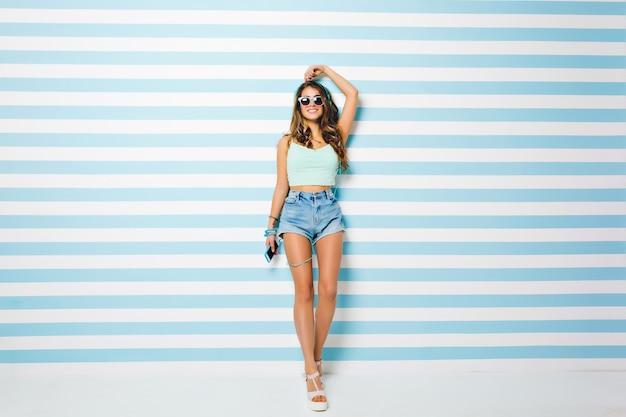 Стройная девушка с модной прической позирует с рукой на полосатой стене, держа телефон. портрет довольной загорелой молодой леди в белых туфлях в солнечных очках и браслетах в полный рост.