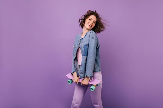 행복 한 미소로 포즈 매끈한 잘 생긴 소녀. longboard 실내 놀 아 요와 아름 다운 갈색 머리 아가씨입니다.