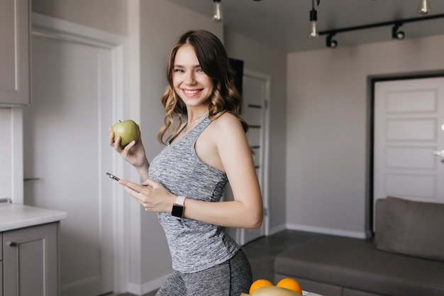 幸せを表現する灰色の衣装で形の良い幸せな女性。リンゴを手にした壮大な少女の室内写真。