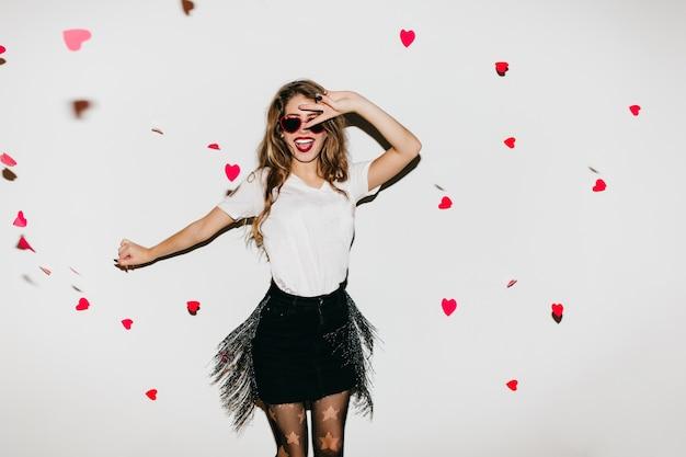 ハートで飾られたスタジオでジャンプする形の良い幸せな女性