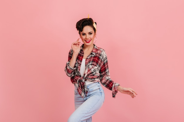 ピンクの背景で踊るジーンズの格好の良い女性。カメラを見ている市松模様のシャツを着たインスピレーションを得たピンナップガールのスタジオショット。