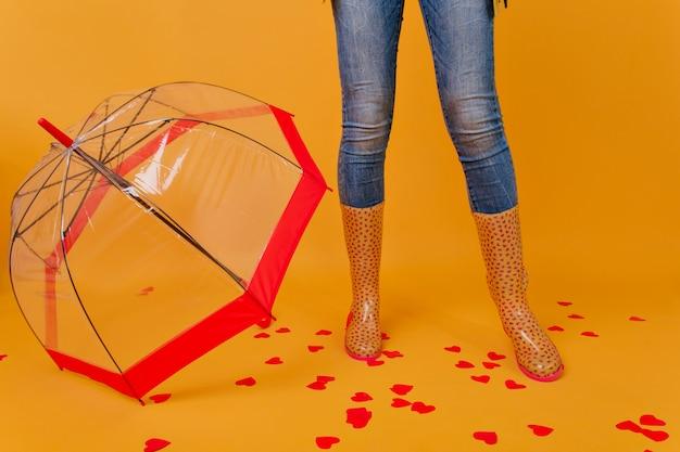 Стройная дама в джинсах стоит возле стильного красного зонтика. фотография в помещении женских ножек в резиновых туфлях рядом с зонтиком.