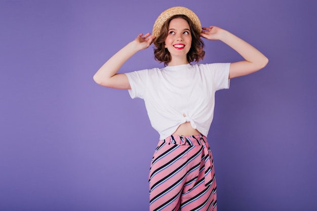 Shapely lady in white t-shirt and vintage hat posing  with smile. indoor photo of glad european girl in striped pants isolated on bright purple wall.
