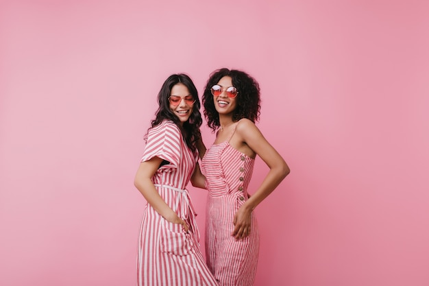 Formosa donna latina in abito a righe in posa con un'amica africana. foto di interni di due donne attraenti che indossano occhiali da sole rosa alla moda.