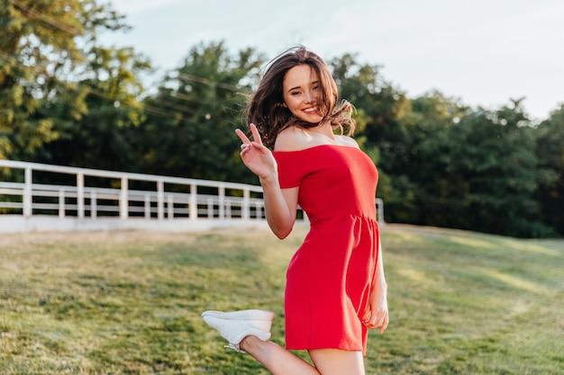 기쁨과 함께 공원에서 포즈를 취하는 빨간 옷에 매끈한 사랑스러운 소녀. 평화 기호 자연에 서있는 드레스에 화려한 갈색 머리 여자.