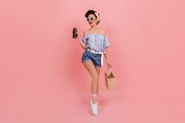 소 다 병을 들고 웃 고 매끈한 핀 업 소녀. 여름 가방 분홍색 배경에 포즈와 멋진 유럽 여자.