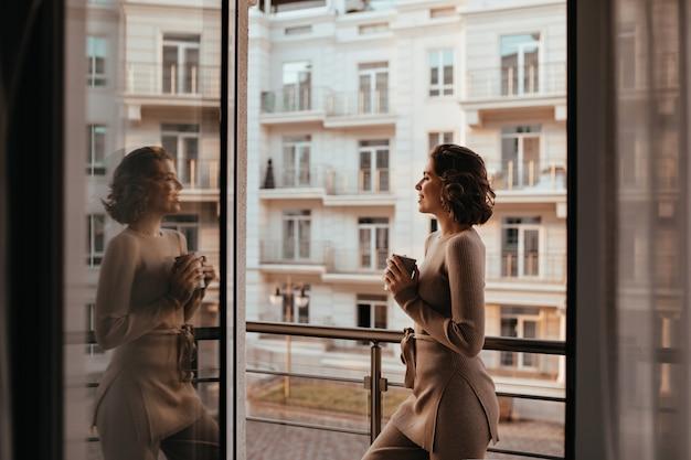 Ragazza formosa e soddisfatta che beve cappuccino e guardando la città. foto della signora di buon umore con una tazza di tè.