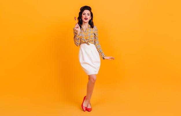 黄色の背景にポーズをとって白いスカートの形の良いきれいな女性。キャンディーを保持しているブルネットのピンナップガールのスタジオショット。