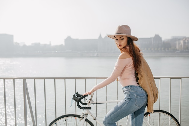 橋を自転車に乗って形の良い赤毛の女性