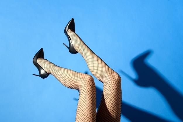 검은 어망과 스틸레토 신발에 슬림 한 여성의 매끈한 섹시한 다리