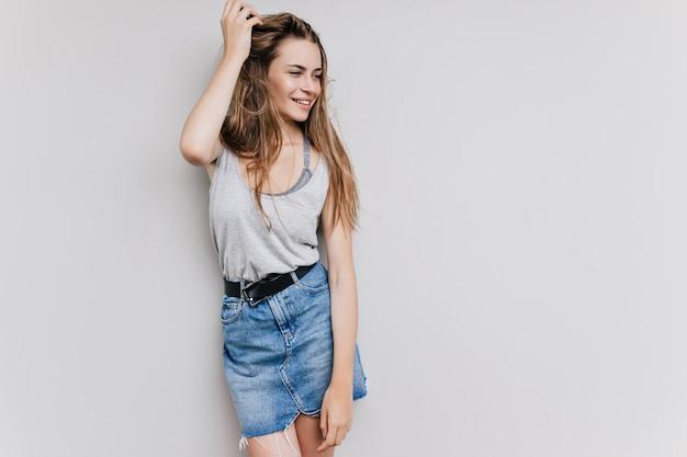 長い黒髪で遊んでいる形の良い見事な女の子。トレンディなデニムスカートの愛らしい白人女性モデルの屋内写真。