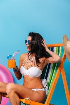 デッキチェアに座って髪に触れる形の良い日焼けした女性