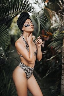 Shapely tanned woman in swimsuit touching neck on nature background. outdoor shot of pretty woman in turban using eye patches.