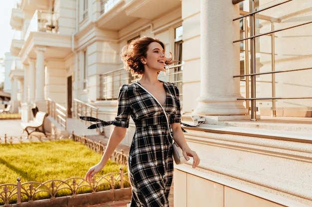 Shapely woman in elegant checkered dress walking down the street and laughing. lovely white female model with short haircut spending time outdoor.