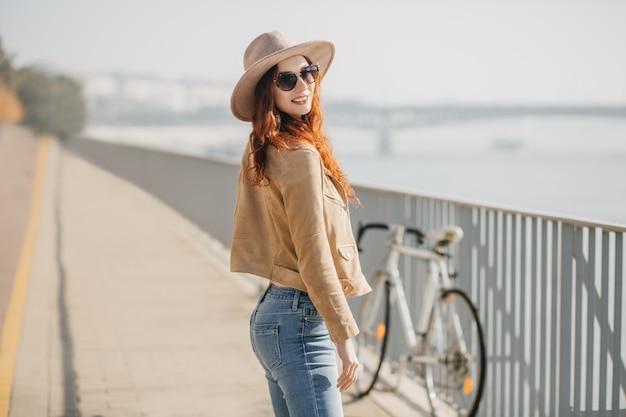 Formosa donna con i capelli rossi godendo il fine settimana nella mattina di sole