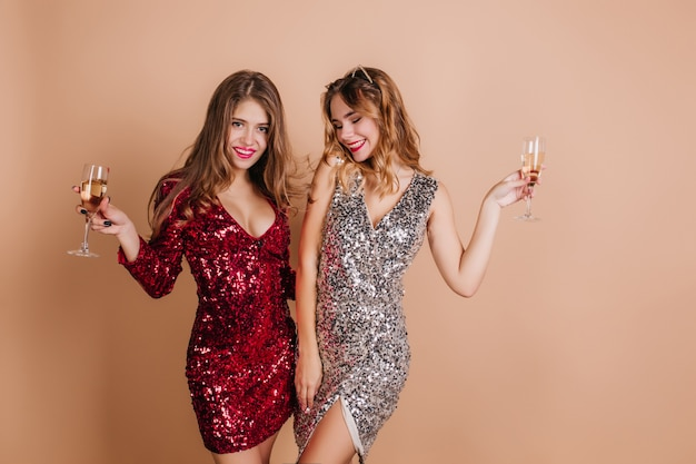 Shapely women in glamorous clothes posing with glasses of wine on light wall