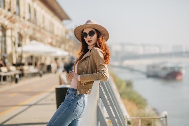 Formosa giovane donna in cappello in piedi vicino al mare e guardando alla telecamera