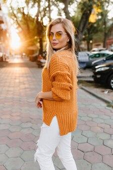 路地を歩きながら肩越しに見ているスタイリッシュな白いズボンの格好の良い若い女性