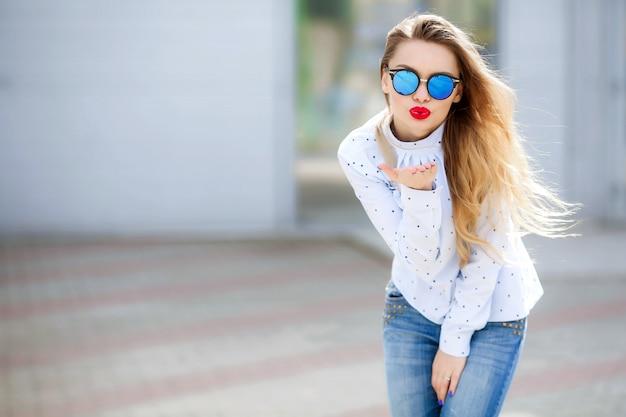 笑顔と目を閉じて屋外でリラックスした長い髪のダンスで格好の良い若い女性。身も凍るようなブロンドの女の子の肖像画