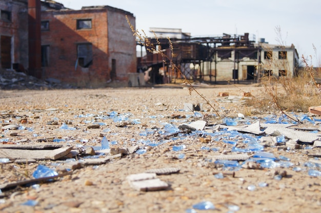 Shards of glass and slate lie on a concrete road abandoned industrial buildings.