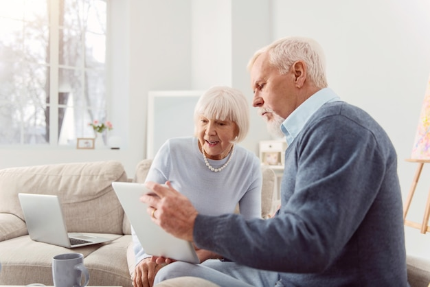 Share your opinion. pleasant bearded elderly man showing his wife a tablet with a social media post open on it and discussing it together with her