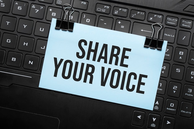 Share your voice inscription on white paper note on laptop keyboard